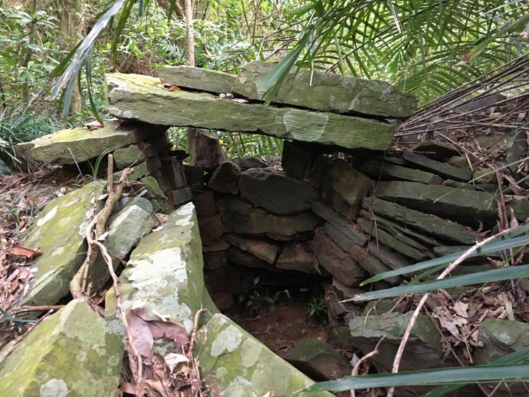 Two large stones being held up by many smaller stones - a person could get inside there