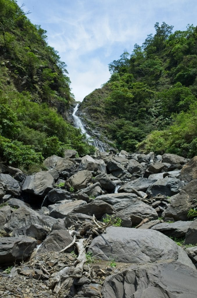 Rocky riverbed with waterfall at top