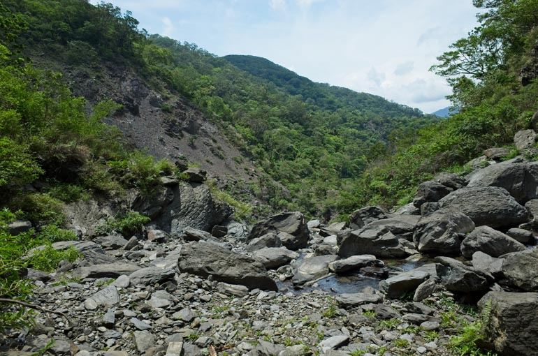 Riverbed view with waterfall behind - rocky