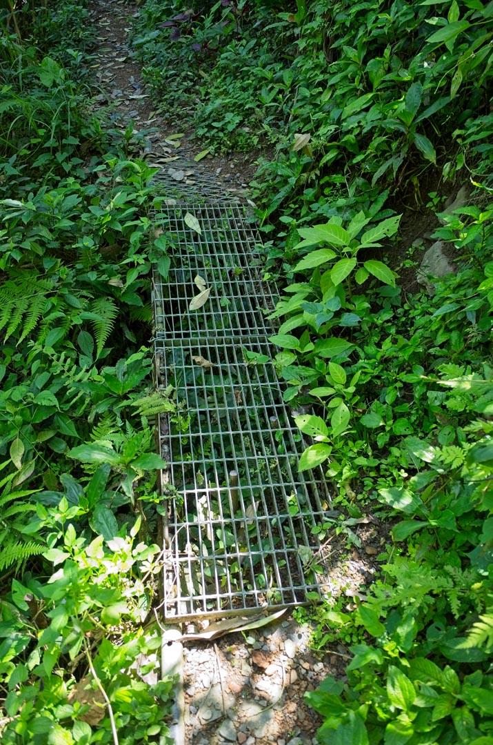 Metal walkway over broken trail