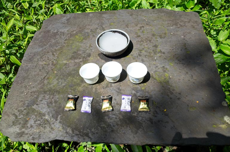 Stone table with cups of water and wrapped candy - appears as an offering