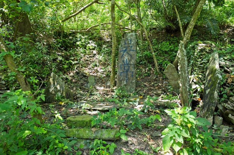 A few tall thin upright stones - one with writing on it