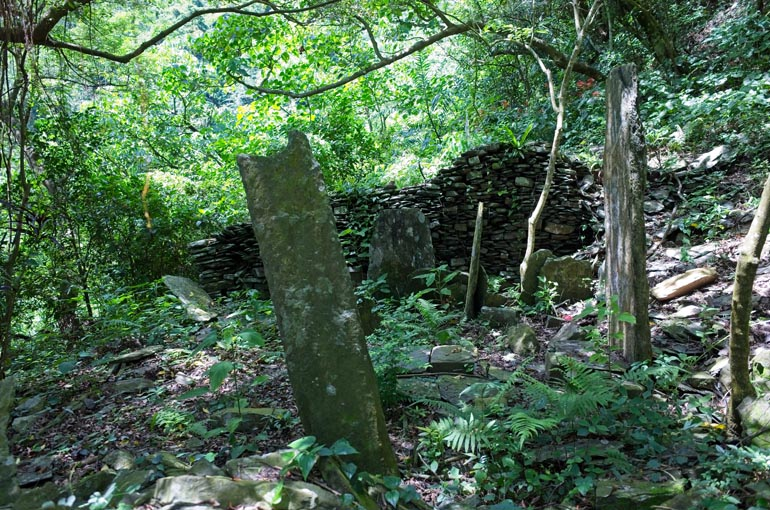 A few tall thin upright stones with stacked rock wall behind