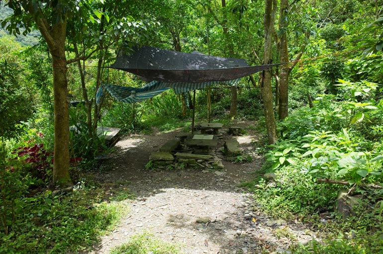 Cleared area with black tarp above and tables and benches made from stacked stones