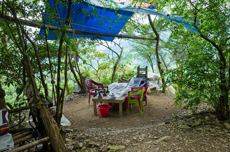 Wooden table - plastic and wooden chairs - cleared area - blue tarp above