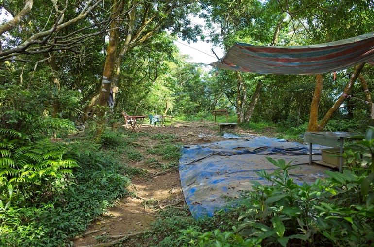 Pengjishan peak - Open dirt area - colorful tarp hung to the side - chairs and tables scattered about