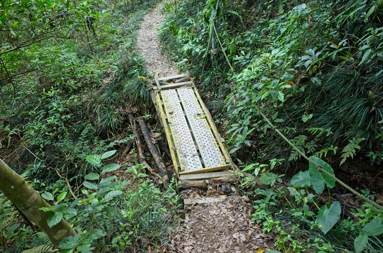 Some sort of metal grating used as a short bridge - rope to the right - trail continues past grating