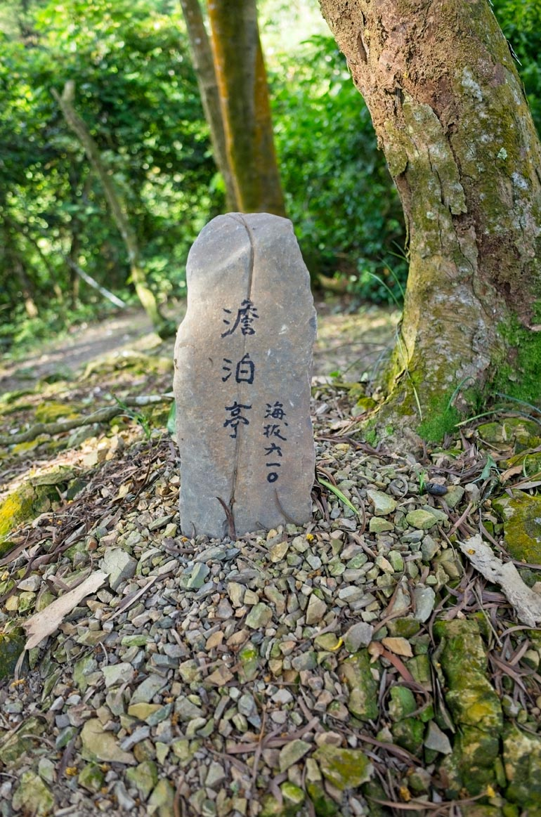 Upright stone placed in the ground with Chinese writing on it