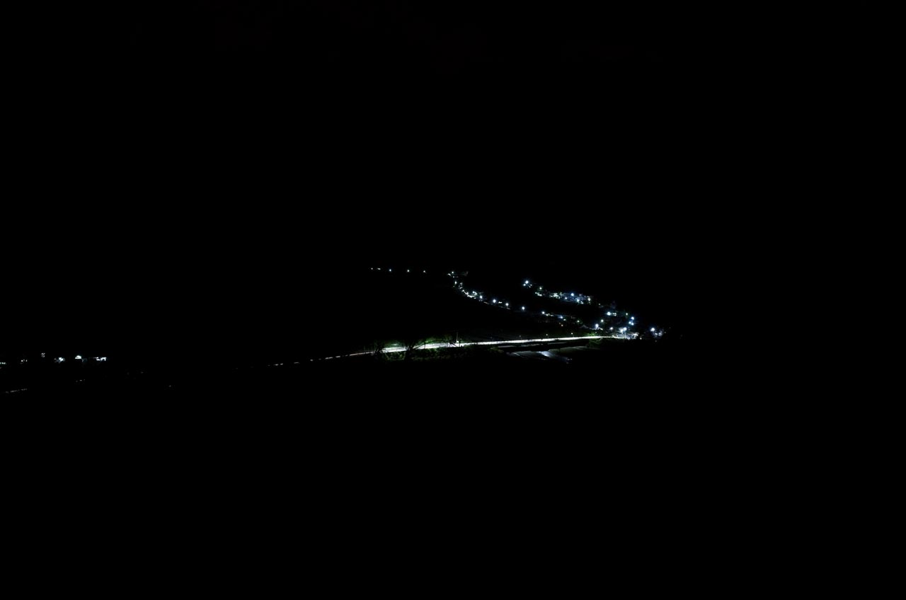 Mostly black - a road highlighted with street lights and some house lights in the distance
